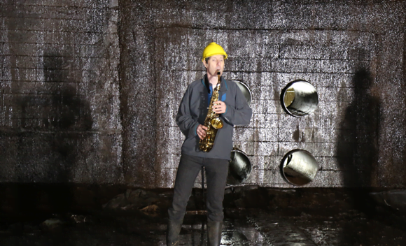 Trevor Cox playing the saxophone in the oil storage tank